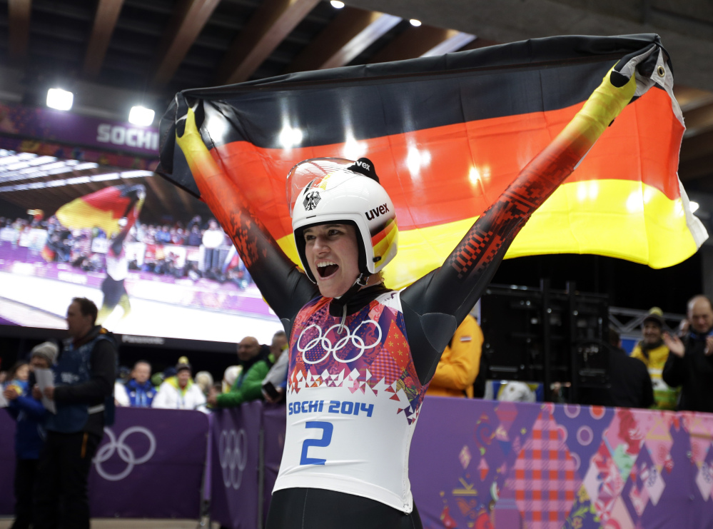 Natalie Geisenberger of Germany waves the flag after finishing her final run to win the gold medal during the women's singles luge competition.