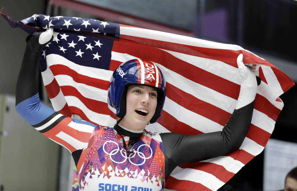 Erin Hamlin of the United States waves the flag after finishing her final run to win the bronze medal during the women's singles luge competition at the 2014 Winter Olympics.