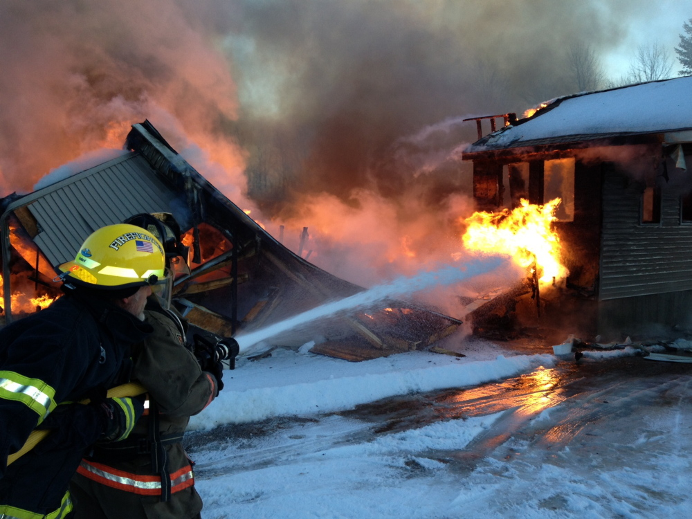 TOTAL LOSS: Firefighters from several communities work at the the scene of a fire Tuesday on Rose Lane in Farmingdale.