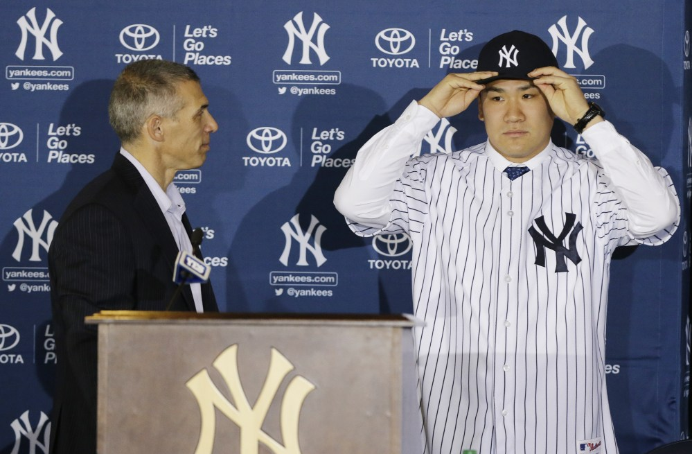 PUTTING ON THE PINSTRIPES: New York Yankees pitcher Masahiro Tanaka puts on his hat and jersey as manager Joe Girardi watches him during a news conference Tuesday at Yankee Stadium in New York.