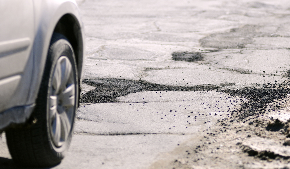 Staff photo by Joe Phelan Cars drive past cracked pavement and filled potholes on Mount Vernon Avenue on Tuesday February 11, 2014 in Augusta.