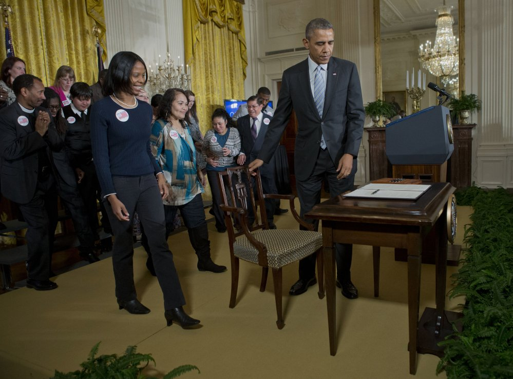 President Barack Obama prepares to take his seat before signing an executive order to raise the minimum wage for federal contract workers, Wednesday, during a ceremony in the East Room of the White House in Washington.