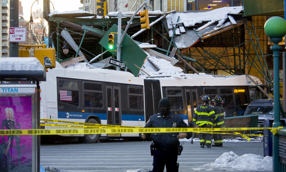 A Metropolitan Transportation Authority bus rests against scaffolding at 14th Street and 7th Avenue in New York, Wednesday, after an early morning collision between the bus and a truck.
