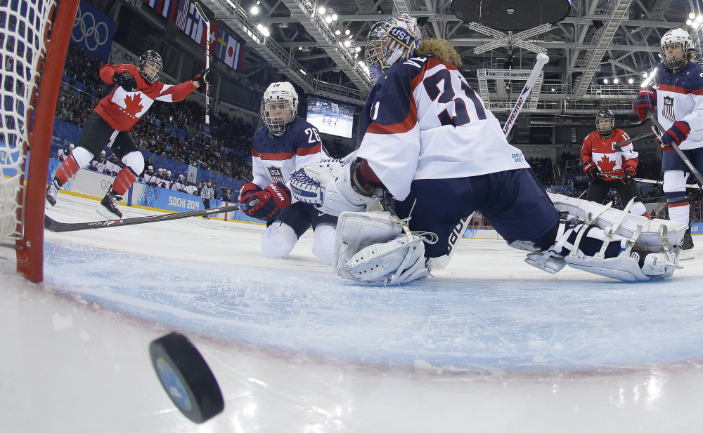 Goalkeeper Jesse Vetter and Kendall Coyne of the United States look back at the puck in the net as Meghan Agosta, left, of Canada celebrates her goal Wednesday at Sochi, Russia. Vetter later gave up a controversial goal as Canada won, 3-2.