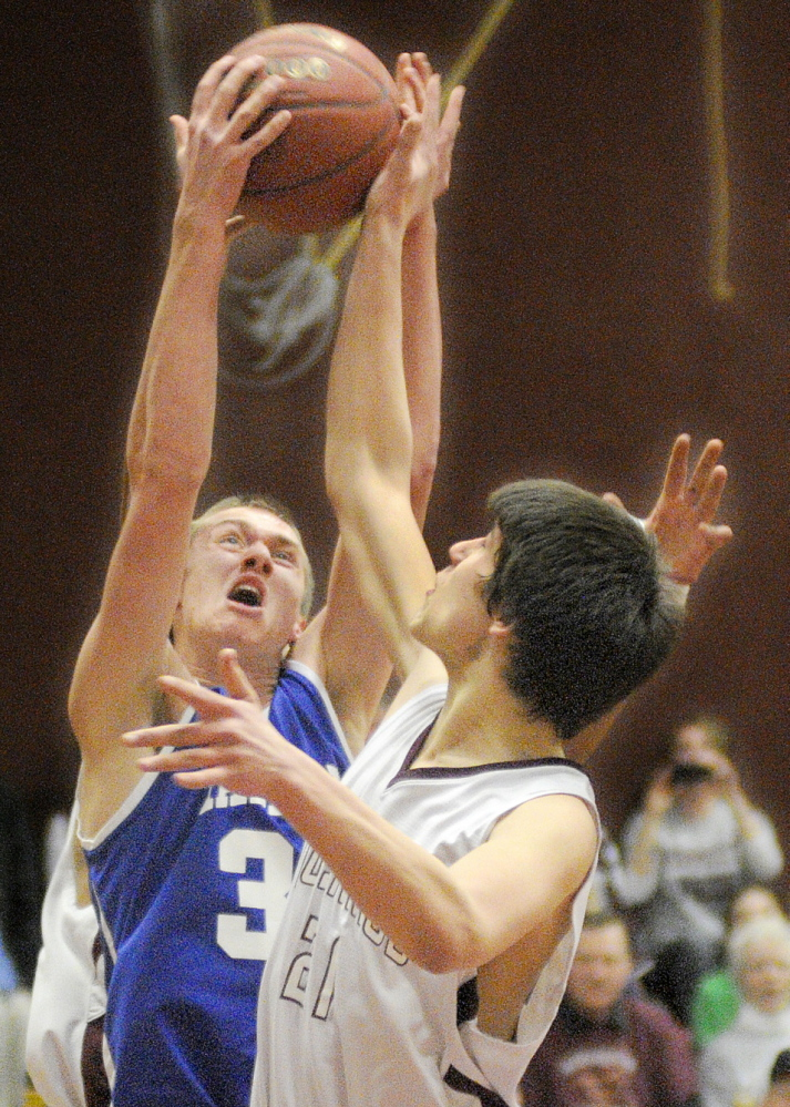 Staff photo by Andy Molloy HARD-FOUGHT AFFAIR: Monmouth Academy's Kasey Smith, right, blocks Madison Area Memorial High School's Dustin West during a basketball match up Wednesday in Monmouth.