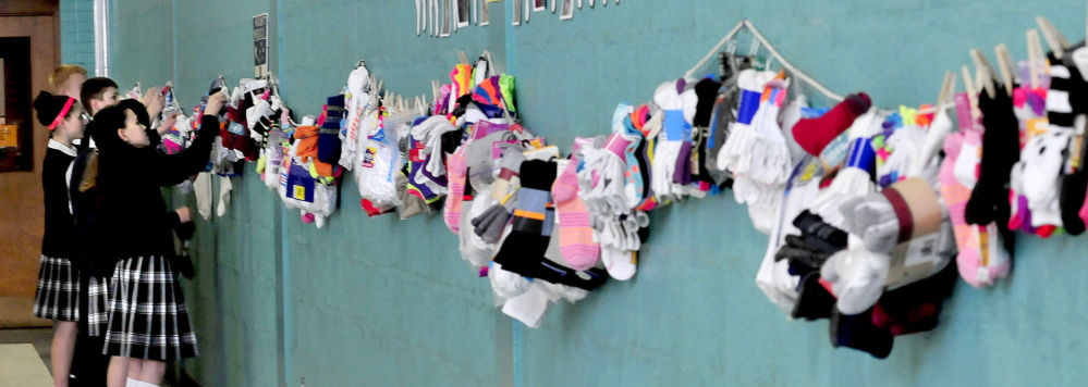 HUNG WITH CARE: Students at Mount Merici Academy in Waterville collected 1,800 pairs of new socks for a Catholic Schools Week service project. The socks will be donated to the Mid-Maine Homeless Shelter. Shown hanging the socks Wednesday are, from right, Lauren Bourque, Sarah Lowell, Mason Violette and Kyle Burger-Roy.