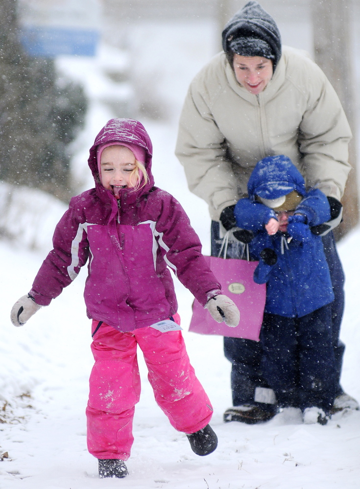 SNOW DAZE: Emerson Hardy, 4, samples a snow flake Thursday while walking home with her brother, Oscar, 2, and mother, Shelby. The trio had walked and shopped near their Hallowell home as the snowstorm arrived.