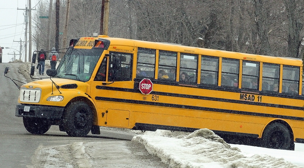 EARLY DISMISSAL: Students leave Gardiner Area High School by bus and foot as snow starts falling around 11:30 a.m. Thursday in Gardiner. Many local schools let out early as a snow storm blew into the area late in the morning.