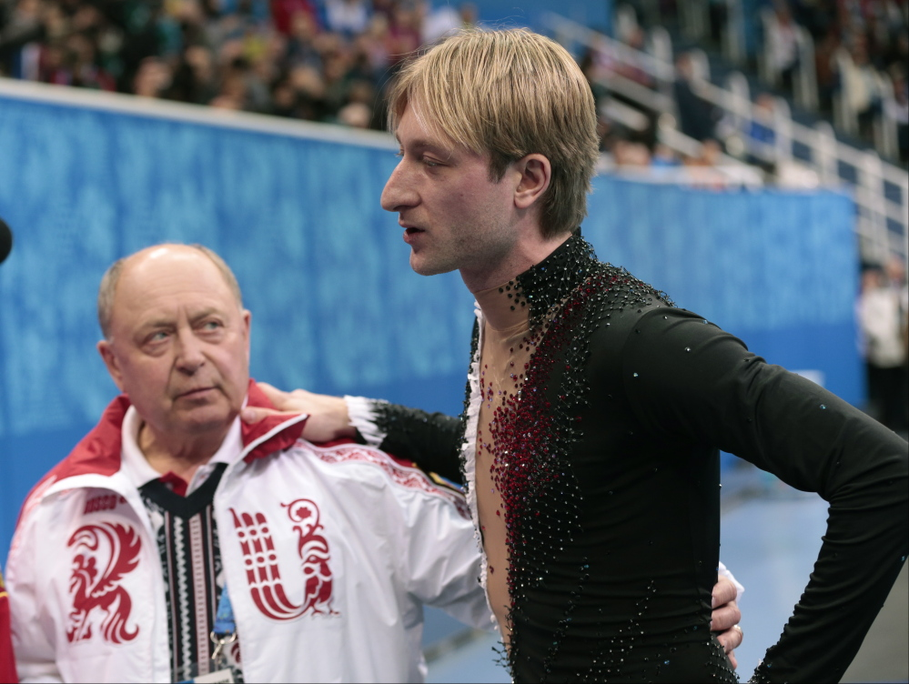 Evgeni Plushenko of Russia and his coach Alexei Mishin leave after Plushenko pulled out of the men's short program figure skating competition due to illness at the Iceberg Skating Palace during the 2014 Winter Olympics on Thursday in Sochi, Russia. Plushenko later announced he will retire.
