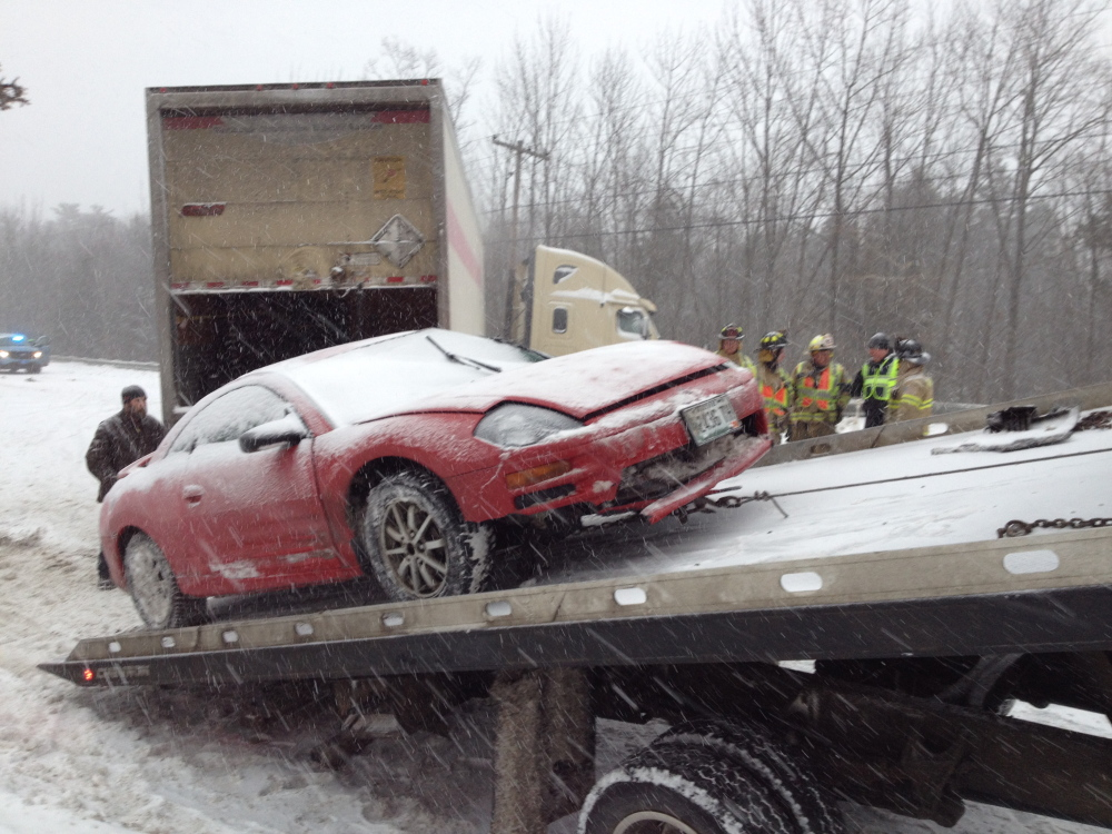 A car is mounted on a flatbed trailer to be towed away following a crash on U.S. Route 202.