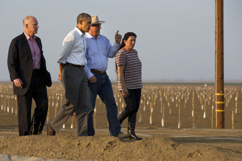 President Barack Obama tours a local farm with California Gov. Jerry Brown, left, and Joe Del Bosque, and Maria Gloria Del Bosque, of Empresas Del Bosque, Inc., in Los Banos, Calif., Friday, regarding the drought.