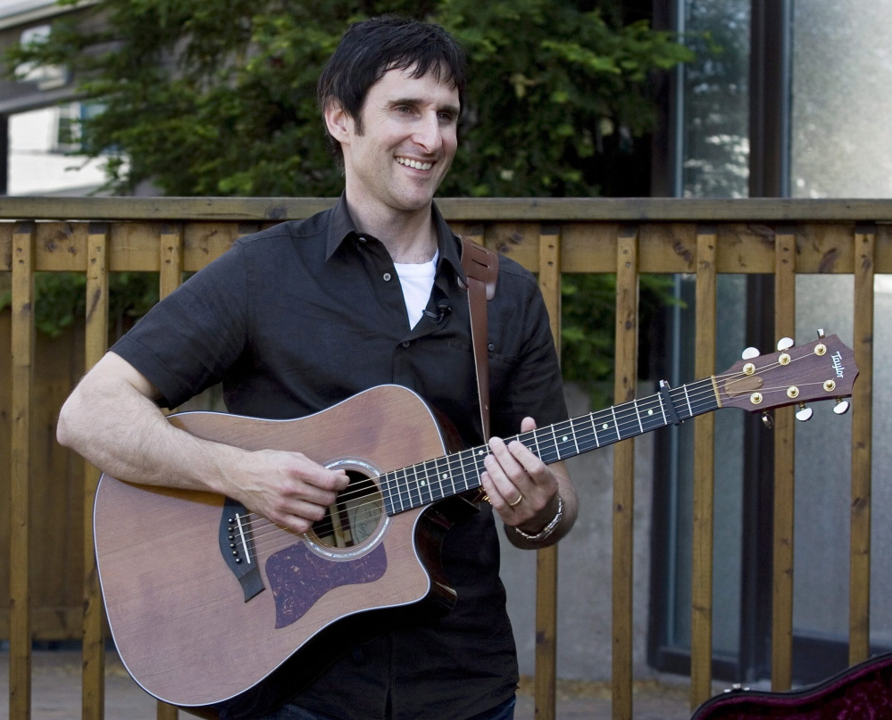 """Musician Dave Carroll, of the pop-folk band Sons Of Maxwell, holds his repaired Taylor guitar in Halifax, Nova Scotia. Carroll became an Internet sensation after posting a revenge song about airline customer service on YouTube with his song """"United Breaks Guitars."""""""