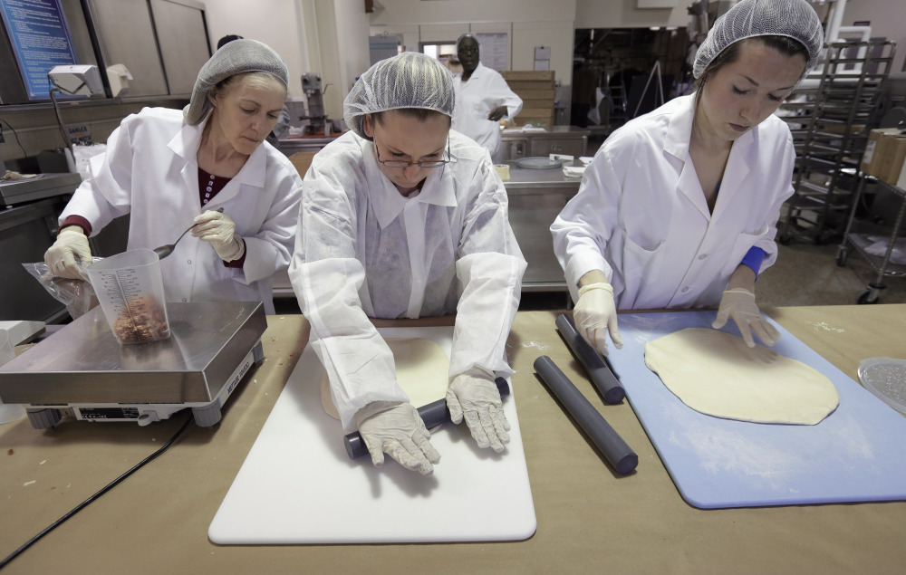 Food researchers Mary Scerra, left, Priscilla Bitopoulos and Lauren Pecukonis prepare ingredients for prototype pizzas in a kitchen at the U.S. Army Natick Soldier Research, Development and Engineering Center, in Natick, Mass.