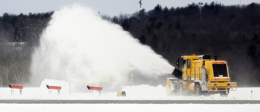 CLEARING THE WAY: A large snowblower works to clean up from the recent snow storm on Friday at the Augusta State Airport.