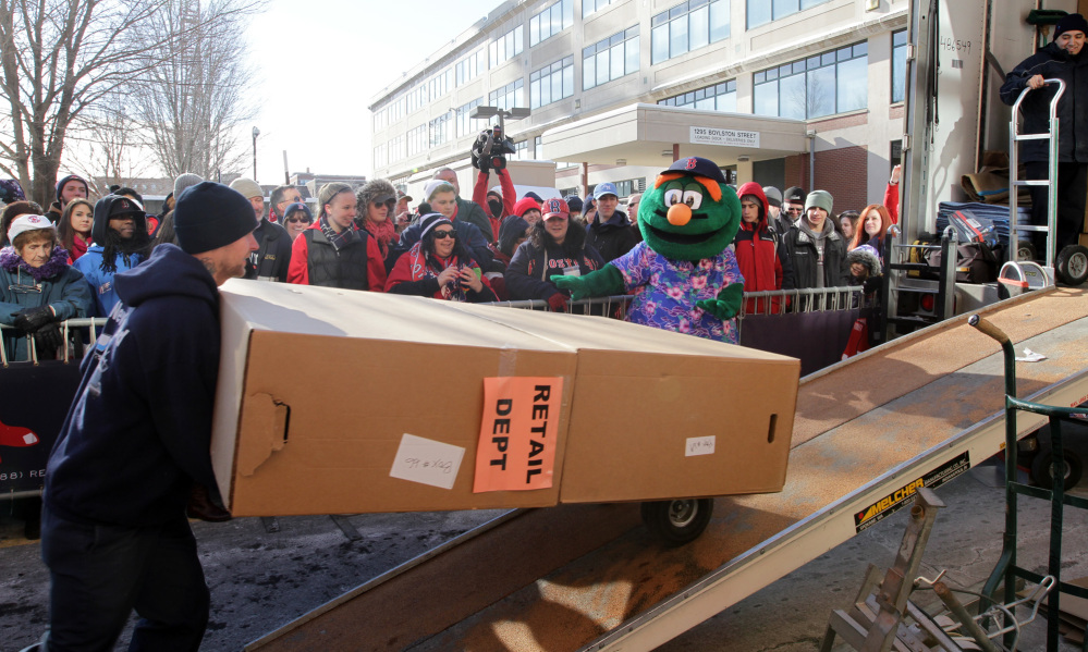 BACK AT IT: Workers load boxes into the Boston Red Sox equipment truck in front of Fenway Park in Boston last week as the team's mascot Wally the Green Monster looks on. The truck left for spring training in Fort Myers, Fla.