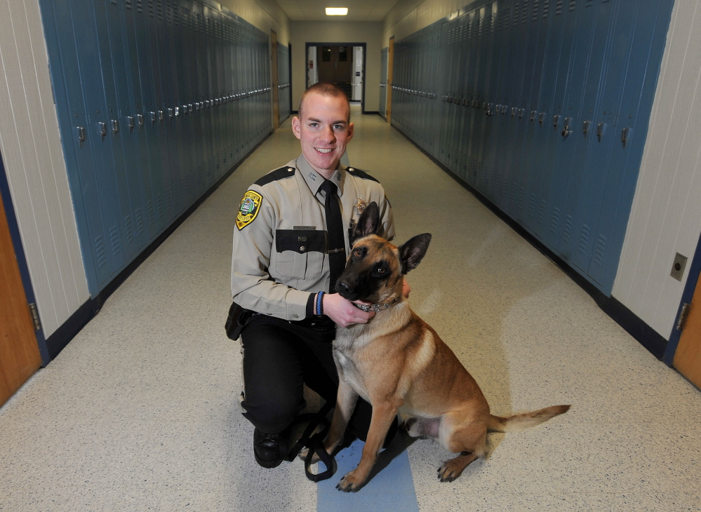 Staff photo by Michael G. Seamans Aaron Moody, a deputy with the Kennebec County Sheriff's office and his partner Striker, at Lawrence High School in Fairfield on Friday. Deputy Moody is the district's school resource officer.