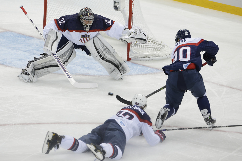 USA goaltender Jonathan Quick defends his goal against Slovakia forward Tomas Tatar as =22= slides across the ice during the 2014 Winter Olympics men's ice hockey game at Shayba Arena, Thursday, Feb. 13, 2014, in Sochi, Russia.