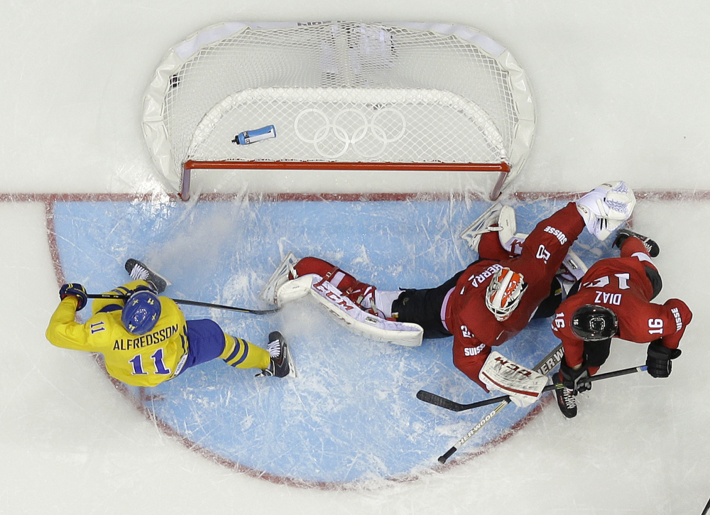 Sweden forward Daniel Alfredsson (11) scores a goal against Switzerland goaltender Reto Berra in the third period of a men's ice hockey game at the 2014 Winter Olympics, Friday, Feb. 14, 2014, in Sochi, Russia. Sweden won 1-0.