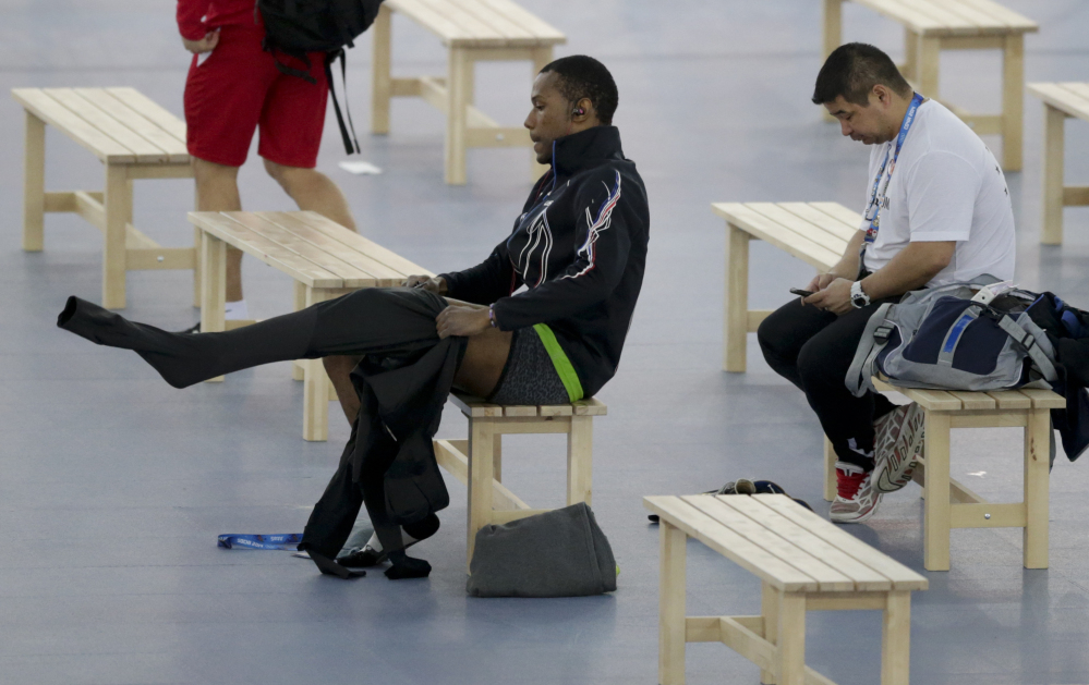 Shani Davis of the U.S., center, puts on the prototype of the official US Speedskating suit, while coach Ryan Shimabukuro checks his phone prior to a training session at the Adler Arena Skating Center at the 2014 Winter Olympics, Friday, Feb. 14, 2014, in Sochi, Russia. The team thought it had a chance to do something special, given some impressive World Cup results this season and new high-tech suits from Under Armour, which got an assist in the design from aerospace giant Lockheed Martin. Now, there's plenty of grumbling that the suits are actually slowing the skaters down in Sochi.