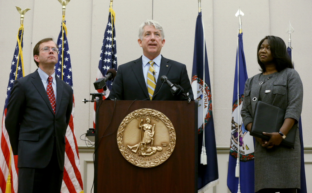 Virginia Attorney General Mark Herring, center, flanked by Solicitor General Stuart Raphael, left, and Chief Deputy Attorney General Cynthia Hudson, right, speaks Friday during a news conference in which he applauded the overnight decision by a federal judge to strike down Virginia's ban on gay marriage.