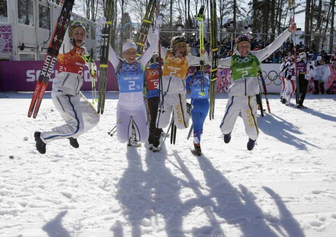 Sweden's women's 4x5K cross-country relay team Ida Ingemarsdotter, left, Emma Wiken, right, Anna Haag, second right, and Charlotte Kalla celebrate winning the gold during the women's 4x5K cross-country relay at the 2014 Winter Olympics on Saturday.