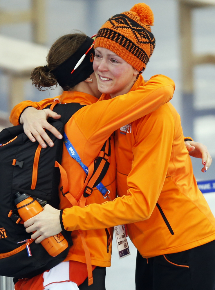 An emotional gold medalist Jorien ter Mors of the Netherlands, right, is congratulated by silver medalist Ireen Wust after the women's 1,500-meter speedskating race at the Adler Arena Skating Center during the 2014 Winter Olympics in Sochi, Russia Sunday.