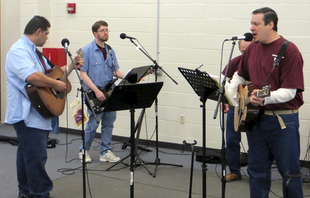 From left, inmates Robert Payzant, Chris Shumway, Steve Carpentier (partially hidden) and Nathan Roy perform during a rehearsal of Sounds of Comfort, a band made up of prison hospice volunteers, at the Maine State Prison in Warren.