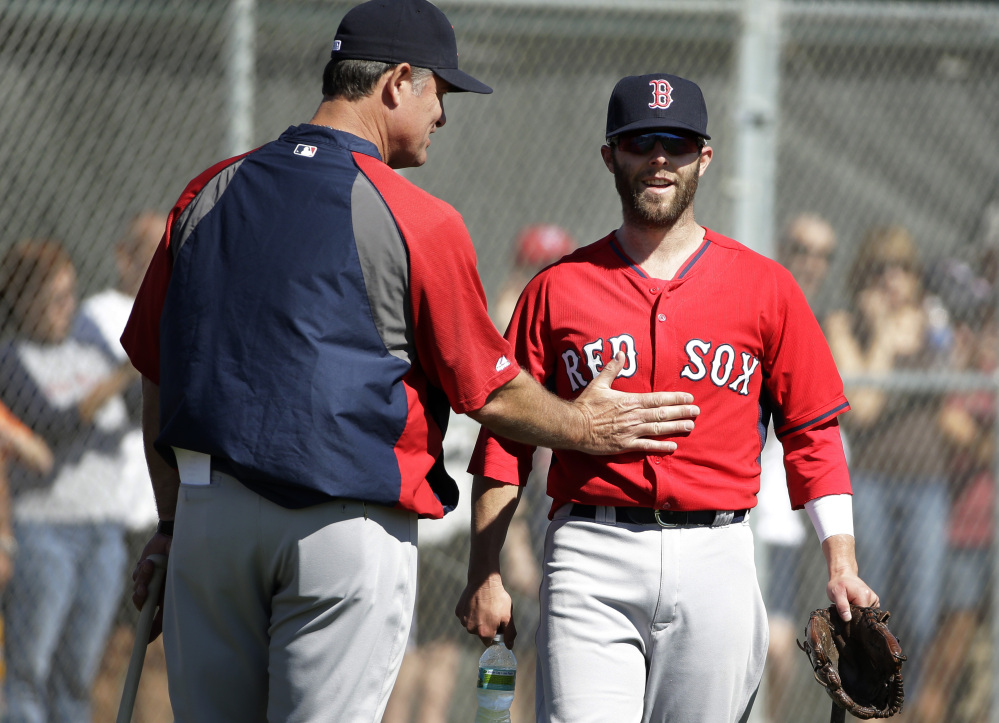 READY TO GO: Boston Red Sox manager John Farrell, left, gives Red Sox second baseman Dustin Pedroia, right, a pat on the stomach during practice Monday in Fort Myers, Fla. Pedroia says he's ready for the season after having offseason thumb surgery.