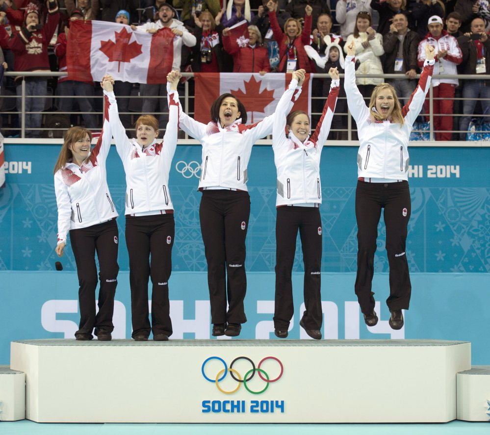 Canada's women's curling team as seen from left to right, Kirsten Wall, Dawn McEwen, Jill Officer, Kaitlyn Lawes and skip Jennifer Jones, celebrate on the podium after winning the women's curling gold medal game against Sweden at the 2014 Winter Olympics, Thursday, Feb. 20, 2014, in Sochi, Russia.
