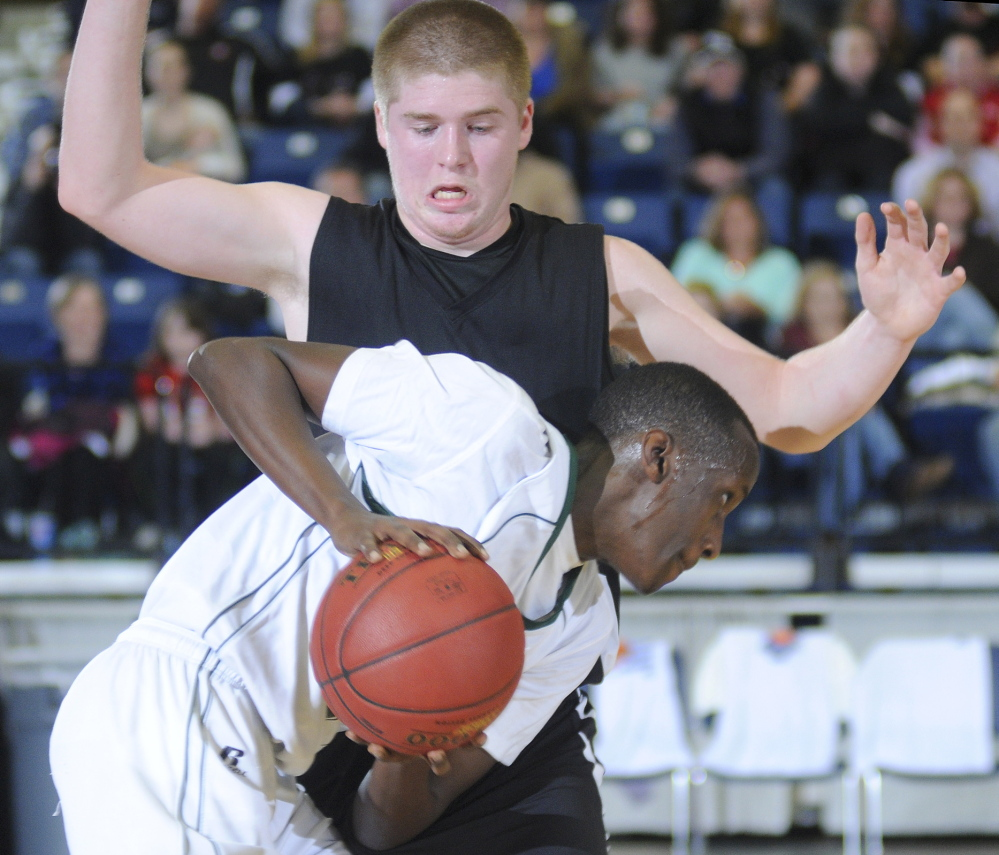 Staff photo by Andy Molloy Hall-Dale High School's Brian Allen blocks Waynflete School's Serge Nyirikamba during a tournament match up Thursday in Augusta.