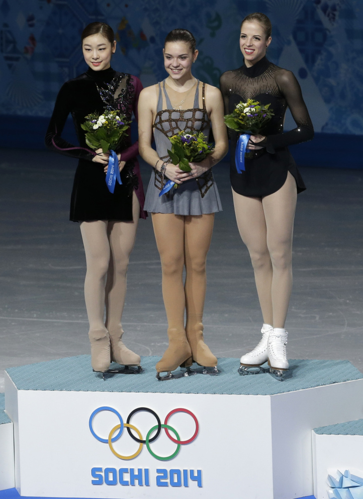 Adelina Sotnikova of Russia, centre, Yuna Kim of South Korea, left, and Carolina Kostner of Italy stand on the podium during the flower ceremony for the women's free skate figure skating final at the Iceberg Skating Palace during the 2014 Winter Olympics