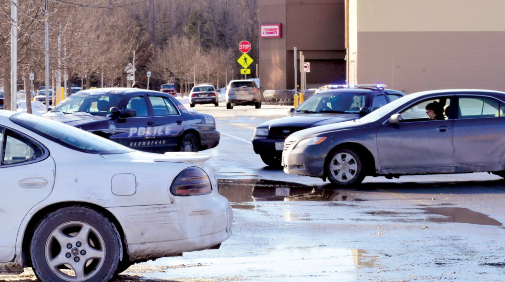 TEMPORARILY CLOSED: Shoppers in vehicles are blocked by police cruisers from entering the Walmart parking lot in Skowhegan as police search the building after a reported bomb threat on Jan. 28.