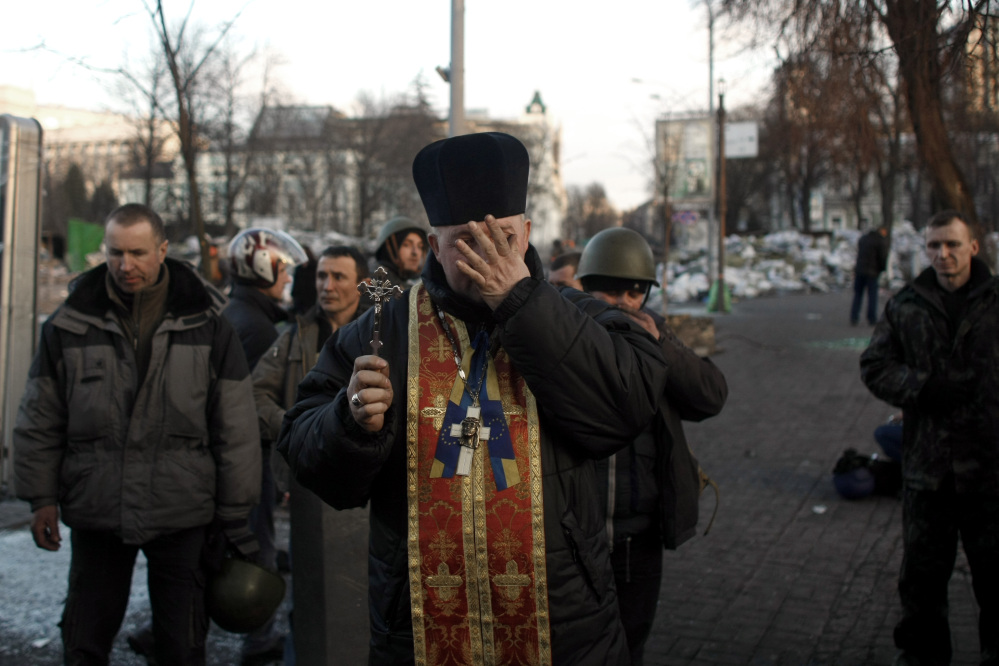 A priest is overcome with emotions as he holds a memorial service for protesters killed during clashes with the police, in Independence Square in Kiev, Ukraine, on Friday.