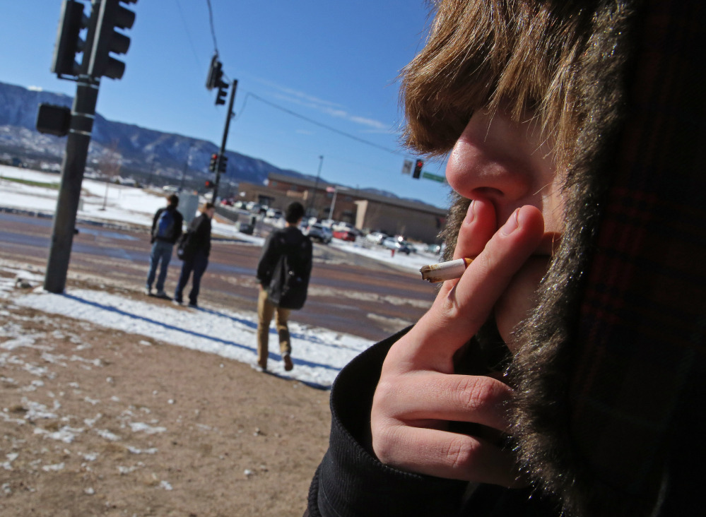 A high school student, who preferred not to be identified, smokes a cigarette in a de facto smoking area just off the property of Lewis-Palmer High School, in Monument, Colo., on Thursday. Colorado already has one of the nation's lowest smoking rates, about 18 percent in 2011, according to the CDC.