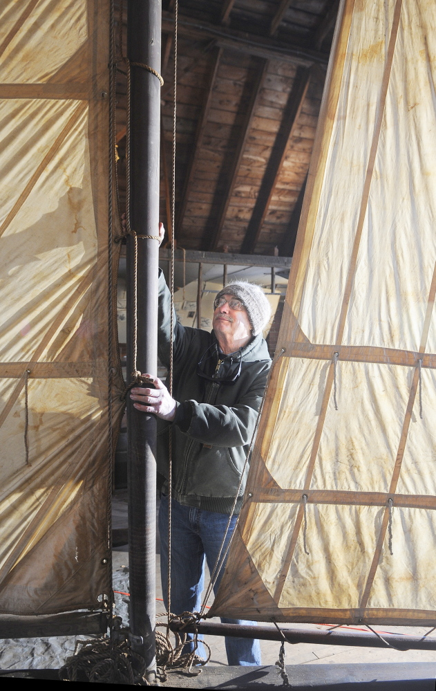 FULL SAILS: Larry Buggia adjusts the mast on the ice boat that was re-assembled on the second floor of the carriage house at the Monmouth Museum. Buggia and other members of the Museum volunteered their time to build the sled that was constructed and raced on Cobbossee Lake in the early 20th Century.