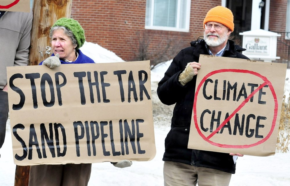 STOP: Marian Flaherty and Dick Thomas were among a group of citizens speaking out against the proposed Keystone XL Pipeline on Sunday, Feb. 23, 2104, in front of the Universalist Unitarian Church in Waterville.