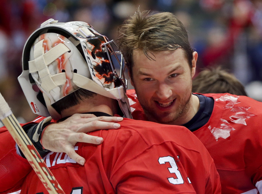 Canada forward Rick Nash congratulates goaltender Carey Price after Canada beat Sweden 3-0 in the men's gold medal hockey game Sunday at the 2014 Winter Olympics in Sochi, Russia.