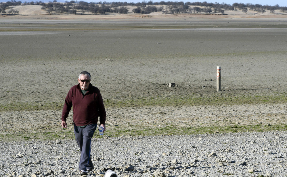 Leon Stout of Orland, Calif., walks across a dry Black Butte Lake near Orland Buttes Recreation Area in Chico, Calif., last month. Meteorologists forecast a pair of storms that could deliver much needed precipitation to parched California, a state that has just endured its driest year in recorded history. Several feet of snow are predicted for the Sierra Nevada.