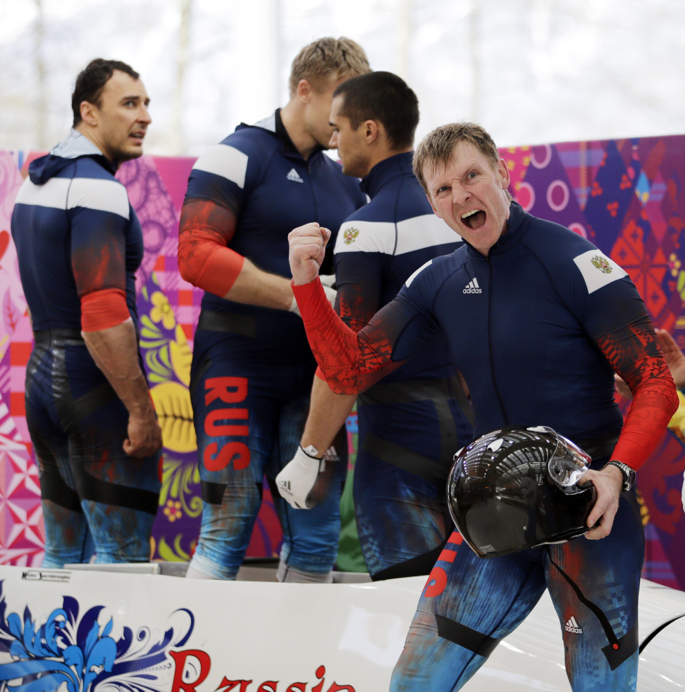 The team from Russia RUS-1, with Alexander Zubkov, foreground, Alexey Negodaylo, Dmitry Trunenkov, and Alexey Voevoda, react after their third run during the men's four-man bobsled competition final Sunday at the 2014 Winter Olympics in Krasnaya Polyana, Russia.
