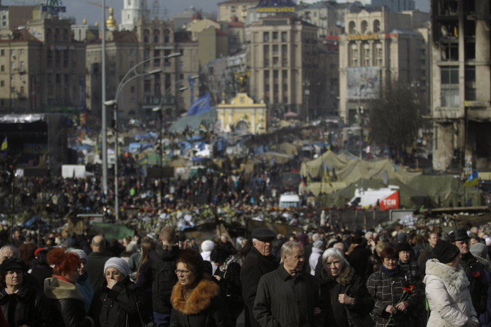 People flock to the Independence Square in Kiev, Ukraine, on Monday. Ukraine's acting government issued a warrant Monday for the arrest of President Viktor Yanukovych, accusing him of mass crimes against protesters who stood up for months against his rule.