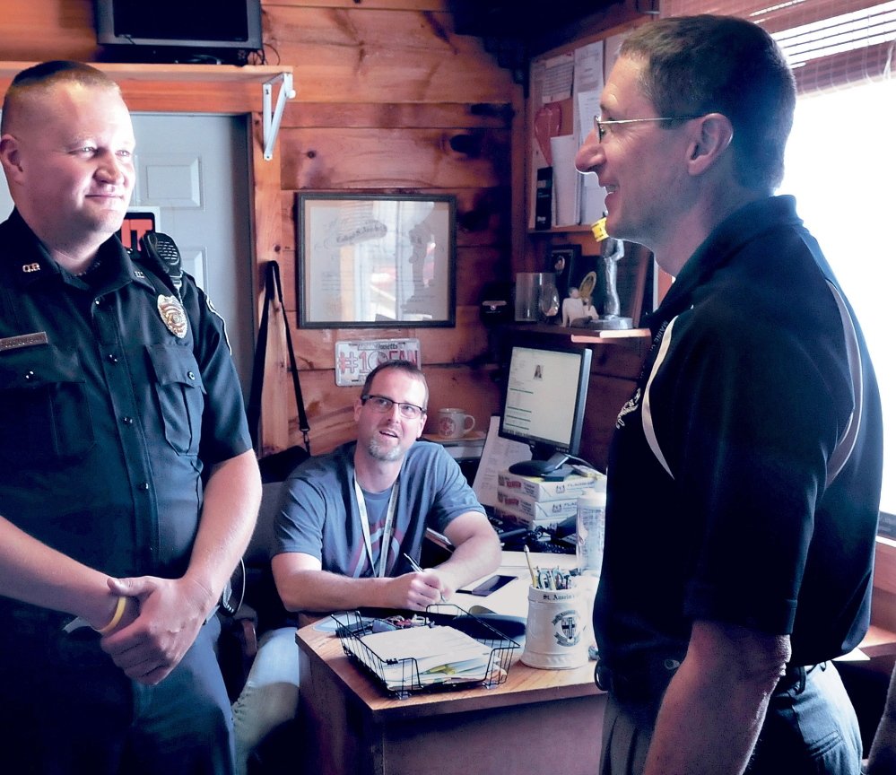 DEPARTMENT HEAD RAISES: Oakland police officer Todd Burbank, left, speaks with Chief Mike Tracy, right, as Capt. Rick Stubbert listens at the department last year. Pay for the positions of Tracy and Stubbert and six others town positions could increase if a proposed budget passes that includes increases in salaries equal to towns of similar sizes.
