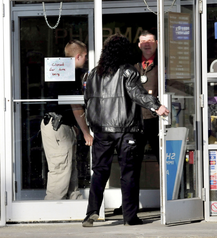 ROBBERY: Police officers open the door to the Rite Aid store in Winslow for Winslow Detective Gina Henderson shortly after the store was robbed on Monday. It was the second time in two years the store was robbed.