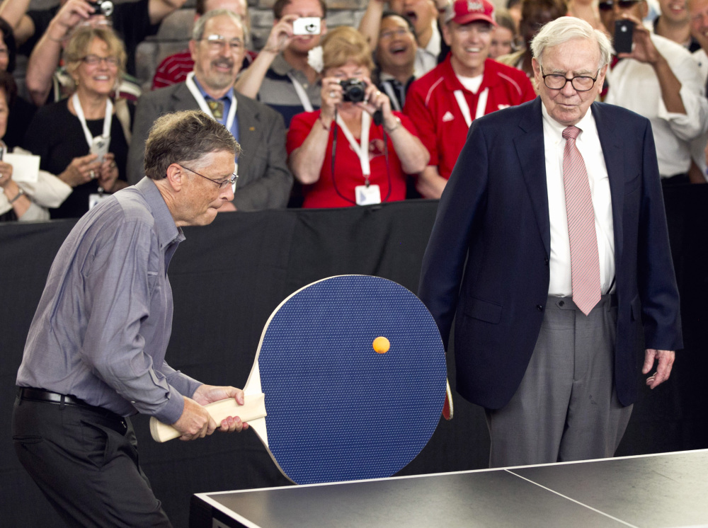 In this May 6, 2012 file photo, Warren Buffett, chairman and CEO of Berkshire Hathaway, right, watches Bill Gates use an oversize paddle as they play doubles against table tennis prodigy Ariel Hsing in Omaha, Neb. Buffet has advocated for a progressive estate tax before members of Congress.