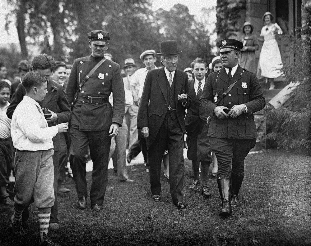 "In this May 14, 1933 photo, John D. Rockefeller Sr. is surrounded by state troopers and admirers as he attends church in Lakewood, N.J. ""Names like Carnegie, Mellon and Rockefeller – the Buffet and Gates of their days – grace universities, museums and medical centers in part because the originators of those fortunes gave back,"" Harvard Business School professor Michael Norton says."