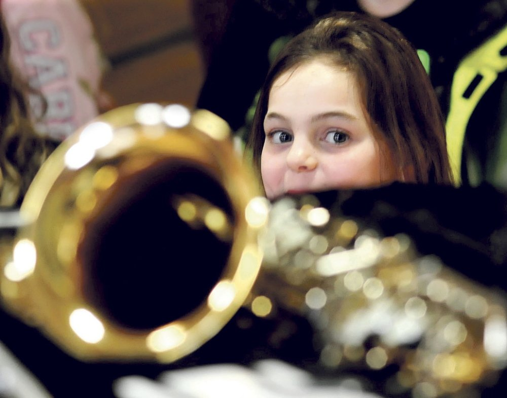THE MUSIC GIRL: Quimby Middle School student Belle Farnham admires some of the musical instruments that were donated by the Cole Land Transportation Museum on Tuesday at the Bingham school.
