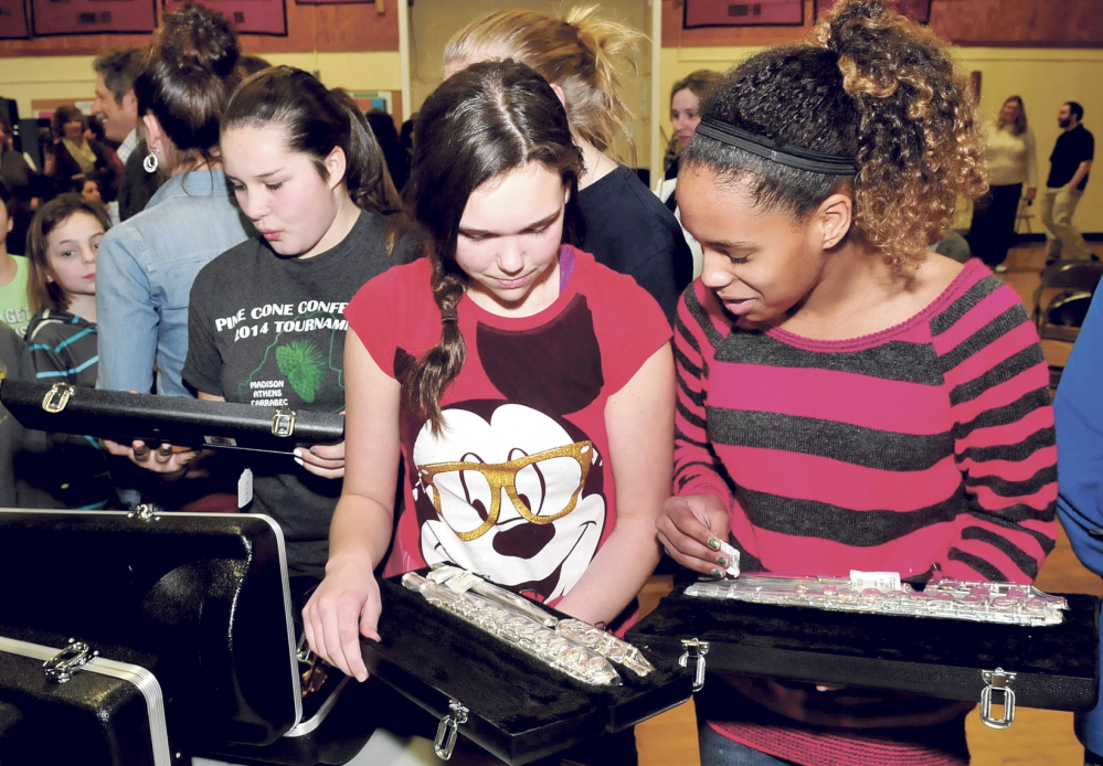 TAKING NOTE: Quimby Middle School students, from left, Ariana Dunton, Rianna Davis and Kendra Sweet look over flutes that were donated by the Cole Land Transportation Museum on Tuesday at the Bingham school.