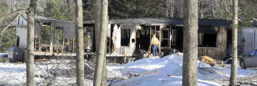 GONE: On Tuesday, a man looks into a mobile home at the intersection of Johnson Flat and Bush roads in Clinton that fire destroyed Monday evening.