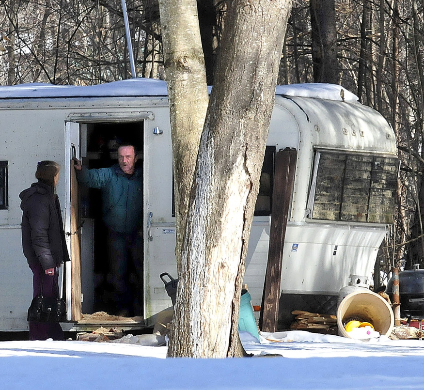 HOMELESS: Homeowner Ken Whitt speaks to a friend on Tuesday from inside a recreational vehicle hours after fire destroyed his mobile home in Clinton. Whitt said he plans to rebuild.