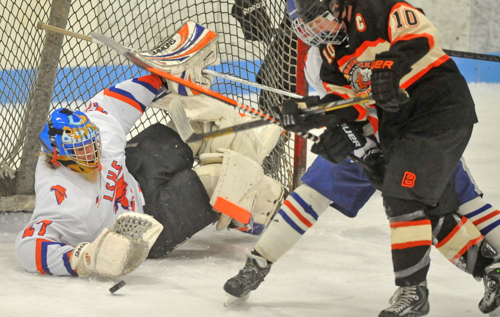 Staff photo by Michael G. Seamans Skowhegan/Lawrence goalie Sam Edmondson, 27, makes a save in as Brunswick High School's Cam Heatley, 10, looks for the rebound in the second period at Sukee Arena in Winslow on tuesday.