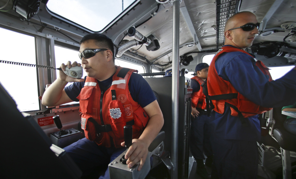 This photo taken Jan. 28, 2014, Coast Guard officer William Pless communicates on the radio while steering the 45 foot Coast Guard vessel through a dense fog during a patrol off the San Diego coast in San Diego.